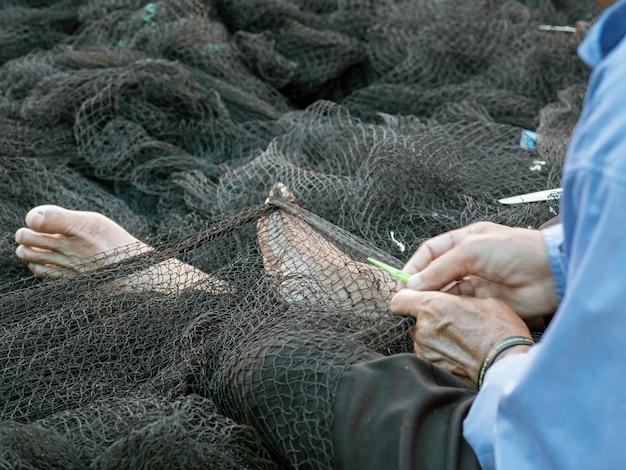 Os pescadores estão reparando redes de pesca, um pescador local no porto reparando redes