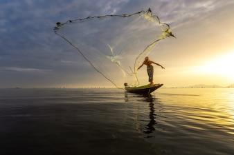 Os pescadores estão usando ferramentas de pesca pela manhã ao longo do lago Songkhla.