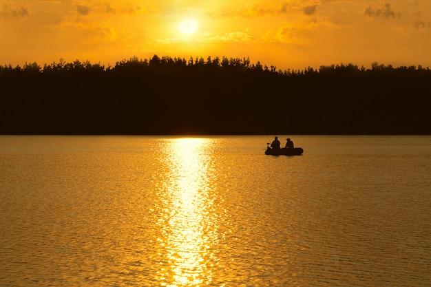 Os pescadores pegam peixes no lago ao pôr do sol.