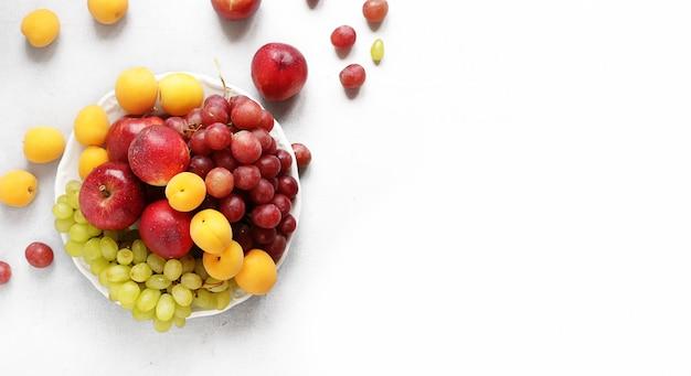 Os pêssegos, os damascos, as maçãs e as uvas da fruta em uma placa branca em um fundo branco copiam o espaço
