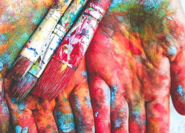 Os pincéis estão nas mãos coloridas pintadas