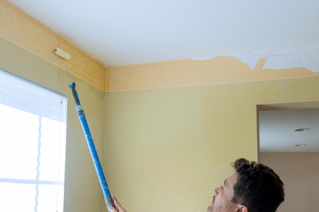 Os pintores estão usando uma escova de rolo de pintura para remover o papel de parede. o homem remove o papel de parede antigo da parede