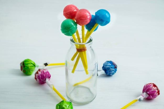 Os pirulitos doces das crianças em cima da mesa