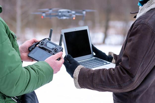 Os planejadores de área examinam os arredores com um drone, close-up de uma mão com um controlador remoto de drone e um laptop, conceito de planejamento e monitoramento de área