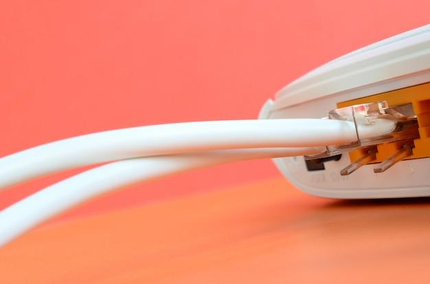 Os plugues do cabo de internet estão conectados ao roteador de internet, que fica em um fundo laranja brilhante