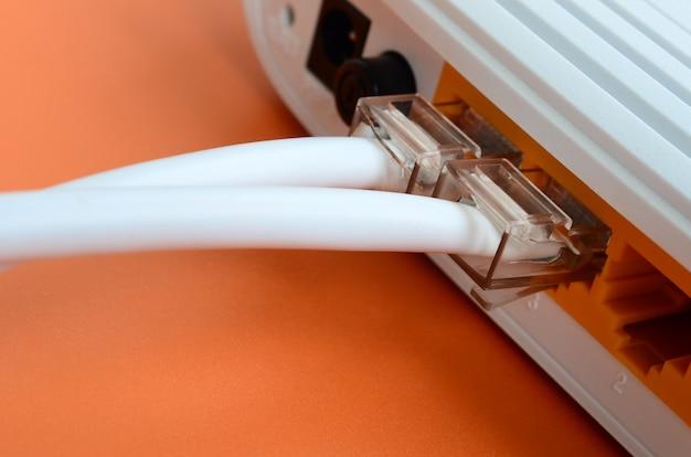 Os plugues do cabo de internet estão conectados ao roteador de internet, que fica em um fundo laranja claro. itens necessários para conexão com a internet