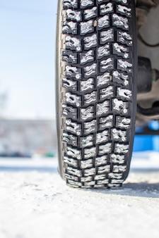Os pneus dos carros na estrada de inverno estão cobertos de neve. um carro em um beco coberto de neve. uma roda de carro na neve.