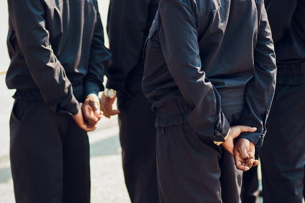 Os policiais da guarda dos pés nas mãos escuras da vista traseira da construção. afro-americanos
