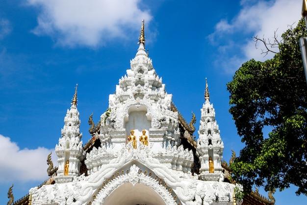 Os portões brancos do templo estão decorados com esculturas do povo lanna