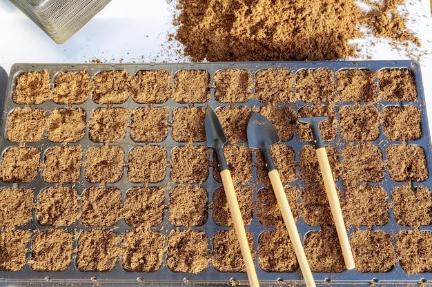 Os potes de plástico estão cheios de turfa. pilha de ferramentas de solo e jardinagem em um fundo branco. preparação para a semeadura.