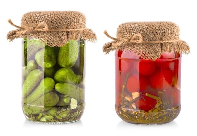 Os potes de vidro com tomates e pepinos com tampa de estopa em um fundo branco