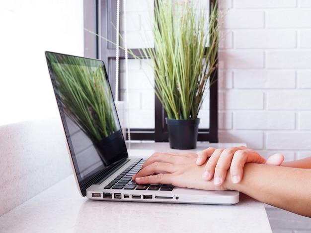 Os povos asiáticos do homem de negócios sofrem da mão e do braço da dor do pulso de trabalhar com o computador portátil.