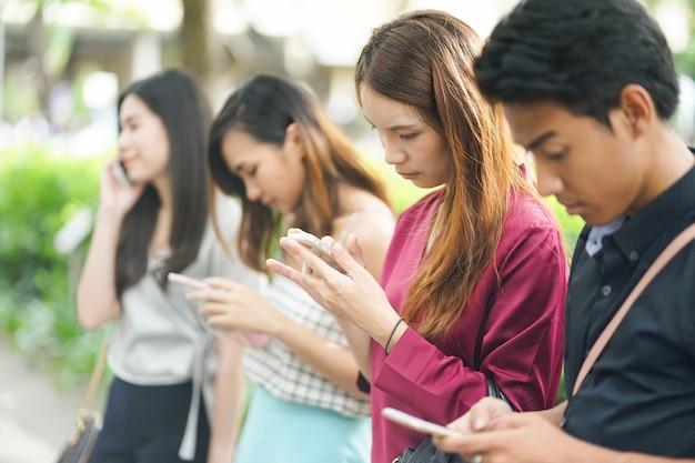 Os povos asiáticos jogam o dispositivo esperto do telefone para o trabalho e jogam a aplicação com amigos