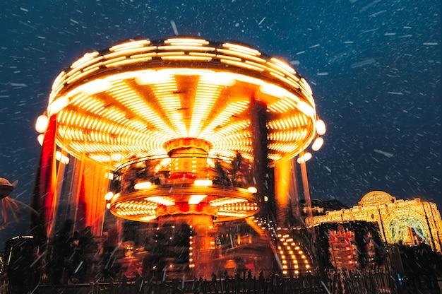 Os povos no carrossel perto do quadrado vermelho decorado e arranjaram pelo ano novo do natal. feira de natal. rotunda luminosa