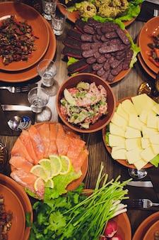 Os pratos de mesa ricamente dispostos da culinária georgiana, muita comida deliciosa, vinho, frutas e carne assada.