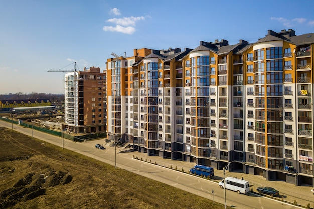 Os prédios de apartamentos altos novos e carros e casas estacionados do subúrbio no céu azul copiam o fundo do espaço.