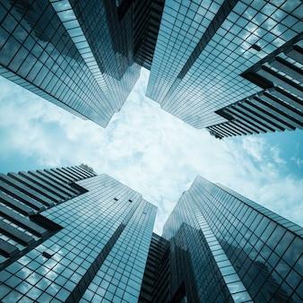 Os prédios de escritórios reflexivos de vidro contra o céu azul com nuvens e o sol iluminam-se.