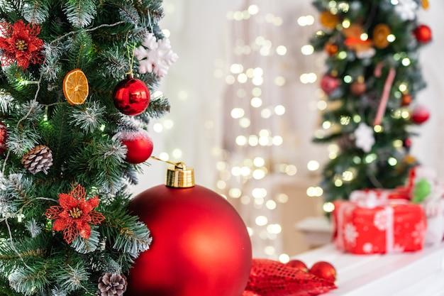 Os presentes de natal e uma grande bola vermelha estão sob uma guirlanda de abeto decorada com bolas de flocos de neve de laranjas secas.