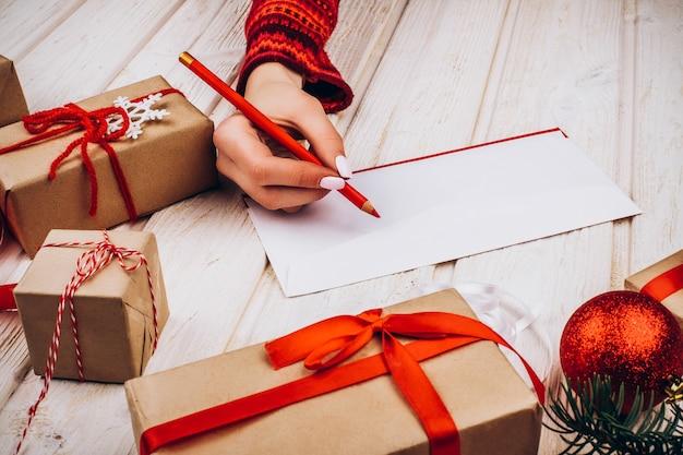 Os presentes de natal em papel marrom com fitas vermelhas ficam na mesa