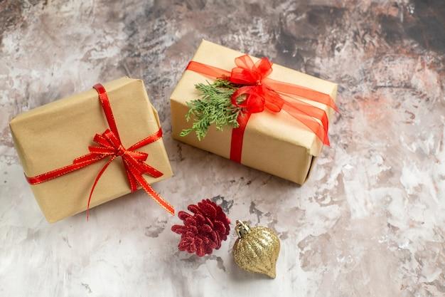Os presentes de natal fofos de vista frontal amarrados com laços vermelhos sobre o fundo claro