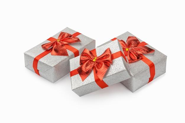 Os presentes em embalagens de prata festivas são amarrados com uma fita vermelha com um laço em uma mesa branca, isolada.
