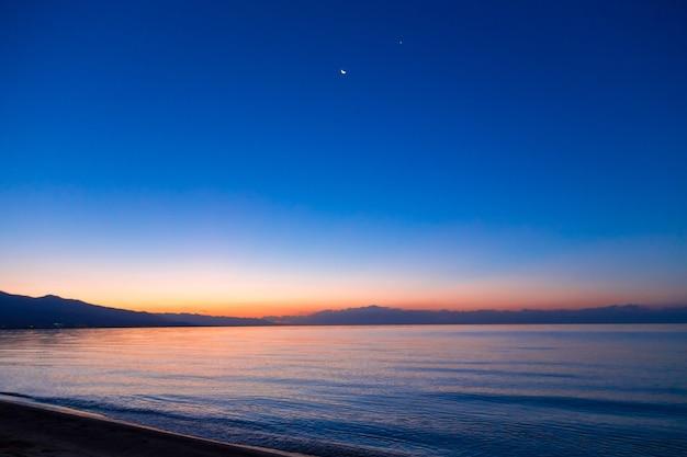 Os primeiros raios do sol nascente contra o fundo do céu escuro da noite