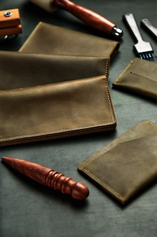 Os produtos de couro estão dispostos na mesa do mestre, em um pedaço de couro entre as ferramentas, acessórios de couro feitos à mão, carteiras de couro da mesma cor.