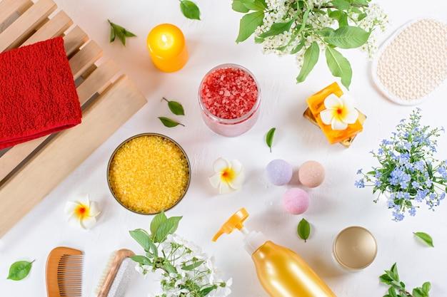 Os produtos e acessórios naturais para o cuidado do corpo são apresentados com flores e folhas. eco spa amigável, conceito de cosméticos de beleza