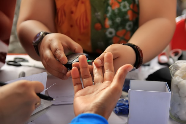 Os profissionais de saúde estão tomando sangue para verificar a saúde dos pacientes em um evento de serviço social de saúde.