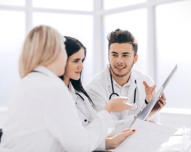 Os profissionais médicos estão discutindo algo sentado na mesa do escritório. o conceito de saúde