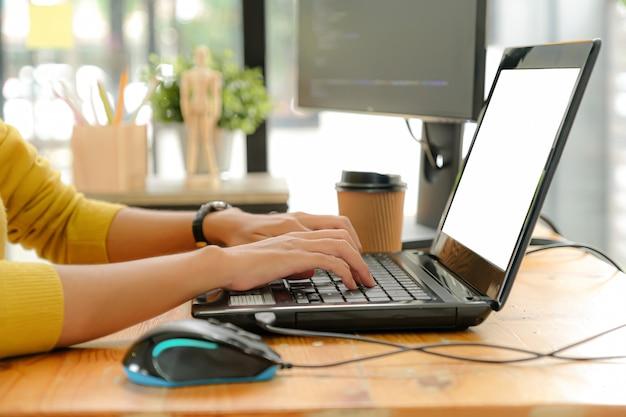 Os programadores estão usando o laptop para escrever programas de acordo com os pedidos dos clientes.