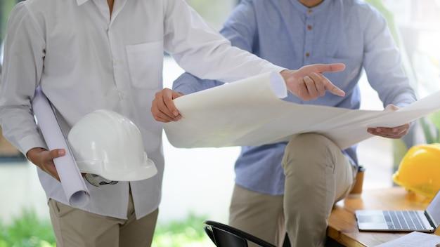 Os projetistas e construtores visualizam as plantas das casas para planejar os trabalhos de construção.