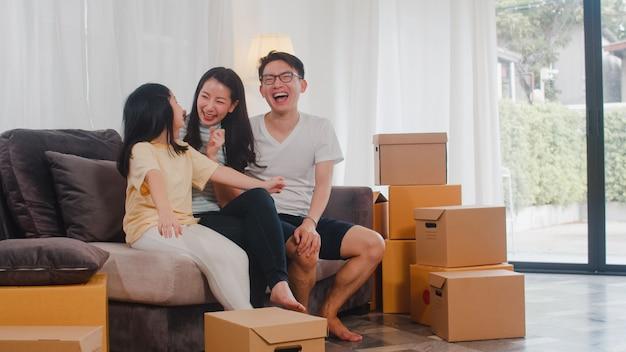 Os proprietários de família novos asiáticos felizes compraram a casa nova. mãe japonesa, pai e filha abraçando ansiosos pelo futuro em nova casa depois de mudarem-se para a internação, sentado no sofá com caixas juntos.