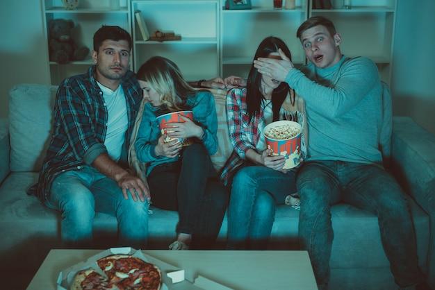 Os quatro amigos com uma pipoca assistem a um filme de terror no sofá