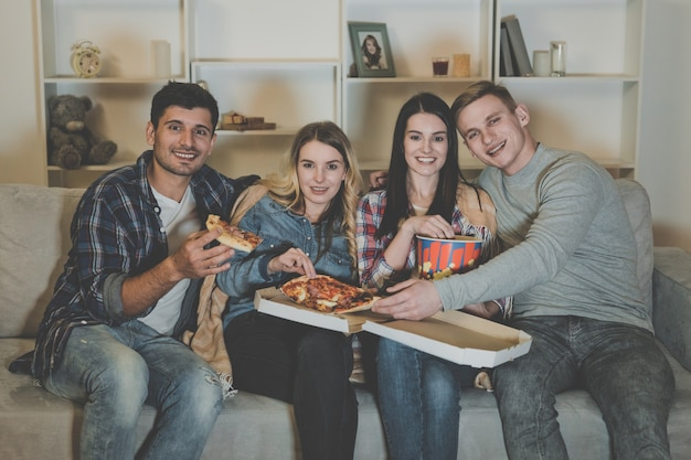 Os quatro amigos felizes com uma pipoca e uma pizza assistem a um filme no sofá