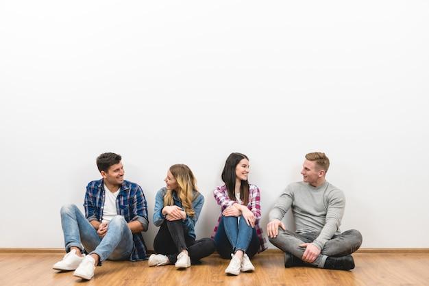 Os quatro amigos felizes sentam-se no chão no fundo branco