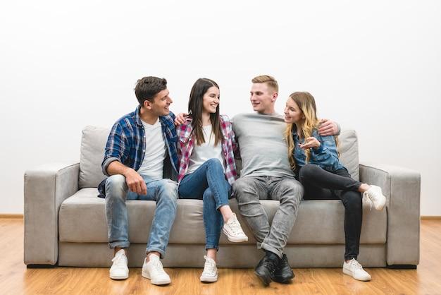 Os quatro amigos felizes sentam-se no sofá sobre um fundo branco de parede