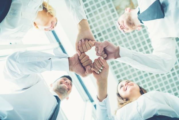 Os quatro executivos felizes cumprimentando com um punho
