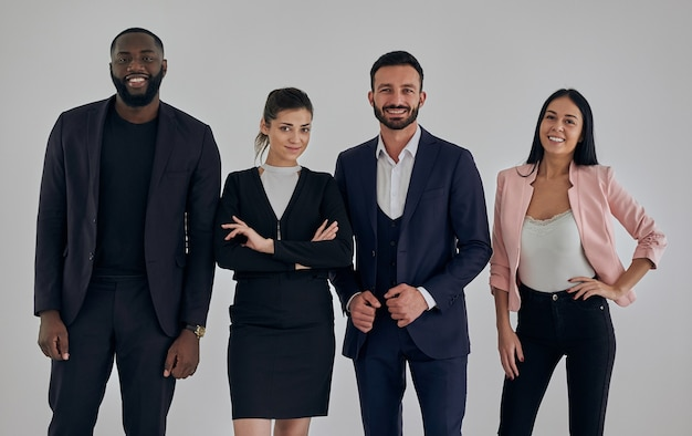 Os quatro executivos felizes em pé perto da parede