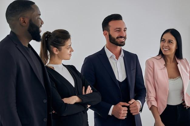 Os quatro executivos internacionais em pé perto da parede
