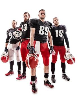 Os quatro homens caucasianos de fitness como jogadores de futebol americano posando de corpo inteiro com uma bola no fundo branco