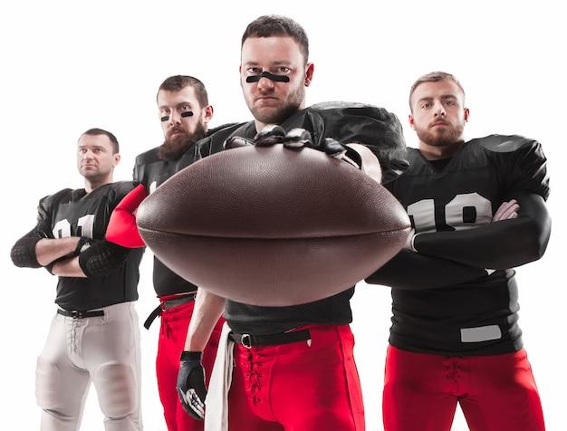 Os quatro jogadores de futebol americano posando com a bola no fundo branco
