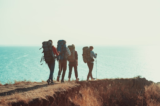 Os quatro turistas com mochilas caminhando ao longo da orla marítima