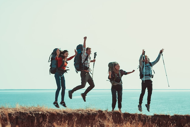 Os quatro turistas com mochilas se divertem na orla marítima