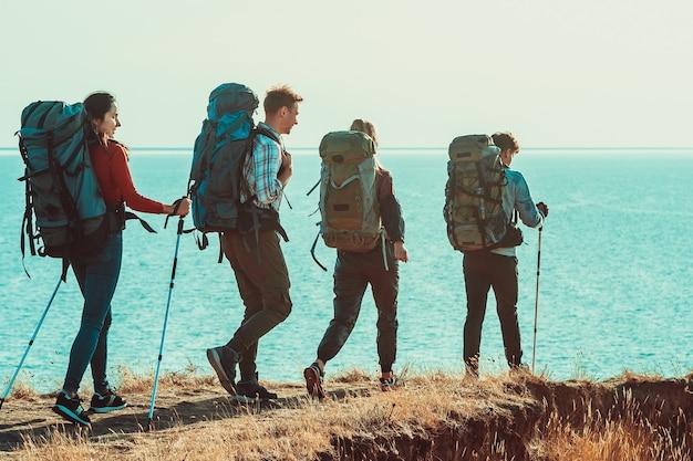Os quatro viajantes com mochilas caminhando ao longo da costa marítima