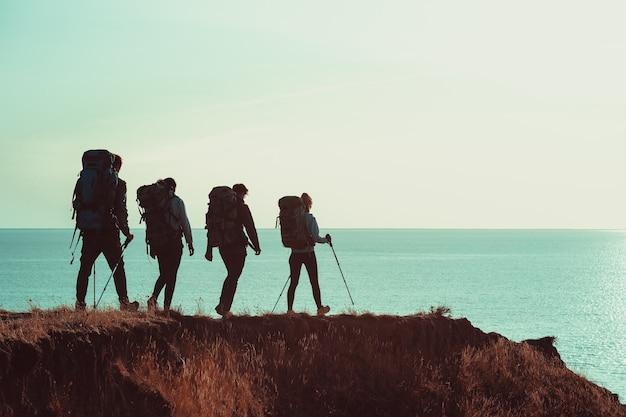 Os quatro viajantes com mochilas caminhando no topo da montanha perto do mar
