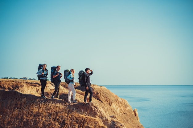 Os quatro viajantes com mochilas no topo da montanha acima do mar