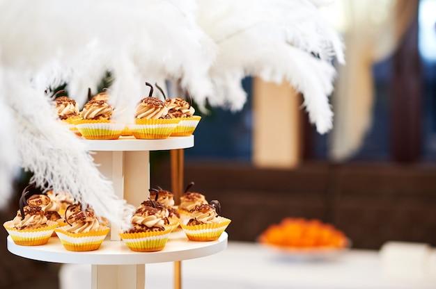 Os queques deliciosos da baunilha do caramelo serviram no conceito saboroso doce da sobremesa do açúcar do alimento do copyspace dos confeitos.
