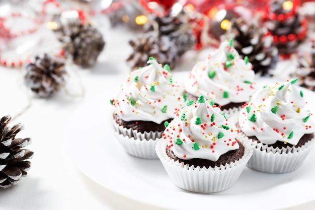 Os queques do chocolate decoraram o creme branco e os abeto em uma placa branca. doces de natal. sobremesa de ano novo