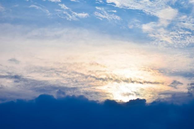 Os raios alaranjados do sol fazem o seu caminho através das nuvens da noite do céu azul do céu azul nublado